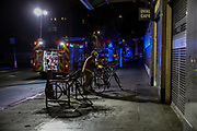 A member of Fire Brigade removes a parked bicycle after an electricity link box, otherwise known as a manhole cover exploded on Monday, Sept 28, 2020 - outside Oval Underground Station in London. No reported injuries. Police, fire brigade and highway maintenance are currently at the scene. The station is currently closed as well as two lanes of Kennington Park Road. (VXP Photo/ Vudi Xhymshiti)