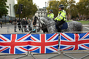 Police horses pass Union Jack flags as Brexit protests continue in Westminster on 30th October 2019 in London, England, United Kingdom. Brexit is the scheduled withdrawal of the United Kingdom from the European Union. Following a June 2016 referendum, in which 51.9% of participating voters voted to leave. As a General Election is passed through the Commons, Brexit protests intensify outside Parliament the day before the original date of leaving on the 31st.