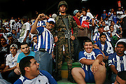 Honduras's national soccer fans celebrate next to a soldier who stands guard before a World Cup qualifier soccer match againt Costa Rica in San Pedro Sula, Honduras, Wednesday, Aug. 12, 2009.