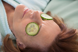 Senior woman with cucumber slices on her eyes, Munich, Bavaria, Germany