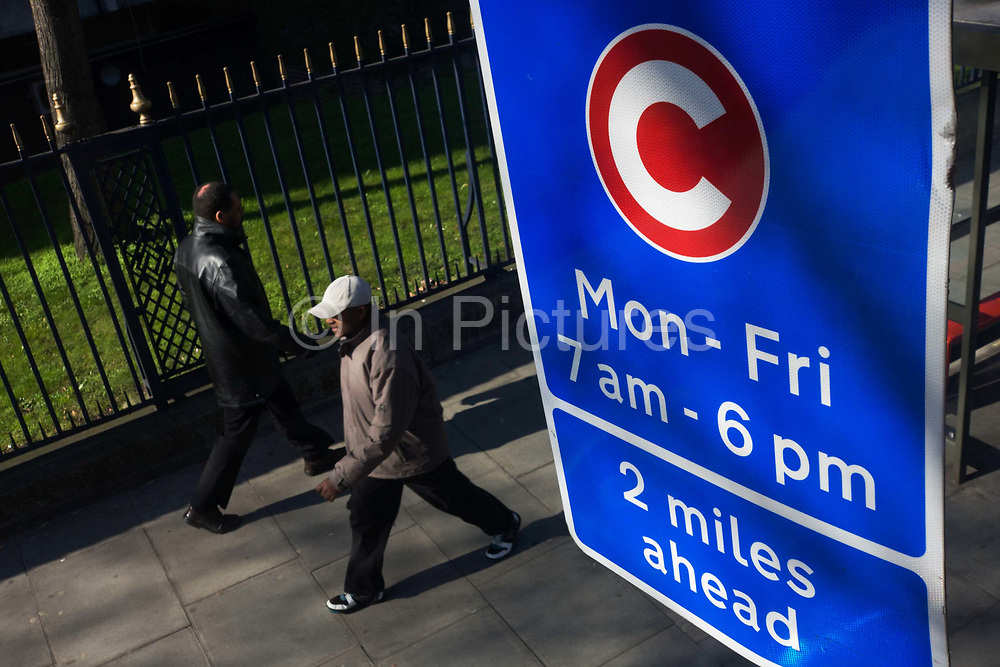 Two pedestrians walk beneath a motorists' Congestion Zone sign on a London street. Seen from the top deck of a bus, we see from an aerial perspective the two men passing each other beneath the taller blue sign which line the capital's congestion zone, a traffic charging area ringing inner London, the boundary of the zone introduced in February 2007 to ease vehicle numbers and pollution and generate extra revenue for transport issues. The bright blue sign tells us that 2 miles down the road, the charge comes into effect from 7am to 6pm, weekdays.