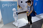 A Japanese man interacts with Softbank's emotional consumer Robot, Pepper on display at the Softbank Store Omotesando, Tokyo, Japan. Friday August 1st 2014.  At the end of June 2021 the Softbank company announced it was cutting jobs in its global robotics business and had stopped production of the Pepper robot.