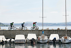 Bikers riding bikes on jetty over lake with sailboats anchored on it