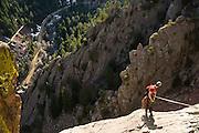 Obadiah Reid prepares to rappel down Redgarden Wall in Eldorado Canyon State Park, Colorado.