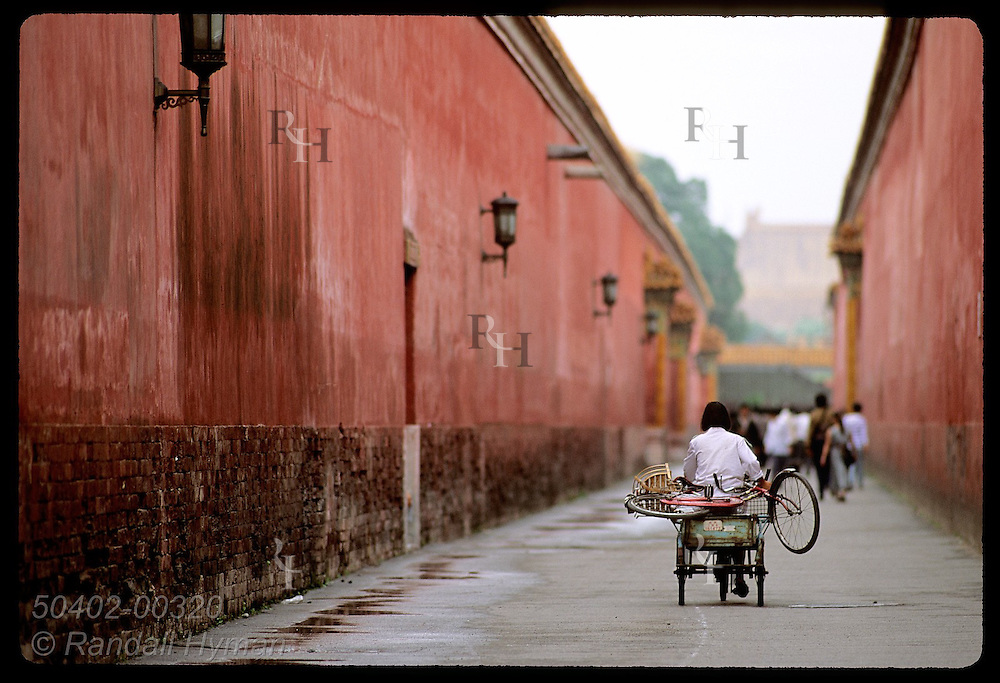 Woman pedals tricycle van, w/ bike on rear, down walled corridor outside Forbidden City; Beijing. China
