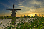 A picturesque windmill at sunrise in the Dutch countryside.
