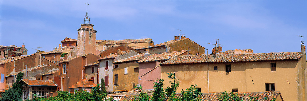 The tones of Rousillion buildings-amber, terra cotta and peach-provide a lovely contrast to the calm blue sky, in Provence, France. ©Ric Ergenbright
