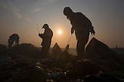 Workers at sunset on Smokey Mountain...RUBBISH DUMP RECYCLING. South East Asia, Cambodia, Phnom Penh. Smokey Mountain, Steung Mean Chey, is Phnom Penh's municipal rubbish dump. Thousands work there, some 600 minors and 2000 adults, recycling the city's rubbish, dumped there by garbage trucks every day. The dump is notorious as many very young children work there. People eat and sleep overnight in the rubbish and fumes, under plastic tarpaulins or in the open air. They work 24 hours a day, like miners, with headlamps at night, collecting plastic, metals, wood, cloth & paper, which they sort and clean, weigh and sell, to be carried away for recycling. A day's work typically brings less than a dollar per person. One and a half to two dollars per day per family. The overpowering, acrid odour of grey smokey fumes blows across the dump, from which the place gets its name 'Smokey Mountain'. It can be smelt miles away. The shantytowns and squats, the recycling worker's homes butt onto or are inside the dump itself. There is no running water, sanitation and many are ill. Children often work with friends or relatives. Religious and ngo's help some children, but this is often resisted by families who need the extra income they generate.///Workers, silhouetted against the setting sun, recycling at sunset in Smokey Mounatin rubbish dump