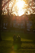 A rear view of two women sitting on a log facing a sinking sun on an Autumn afternoon in south London, on 4th November 2020, in London, England.