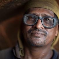 A worker in a boatyard on the Buriganga river, Dhaka, Bangladesh, wearing cracked protective goggles