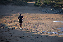 © Licensed to London News Pictures. 27/03/2020. Wadebridge, UK. A jogger on Constantine Bay beach, Cornwall, this morning. British Prime Minister Boris Johnson has ordered a lockdown to slow the spread of Coronavirus (COVID-19) across the country. Photo credit : Tom Nicholson/LNP