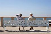 Nederland, Scheveningen, 20-6-2019 Aan de boulevard zit een ouder echtpaar op een bankje naar het strand te kijken . Foto: Flip Franssen