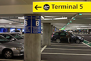 Man closes vehicle door and car park architecture at Heathrow's terminal 5.