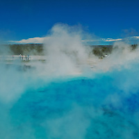 Steam obscures tourists beside Excelsior Geyser Crater in Wyoming's Yellowstone National Park.