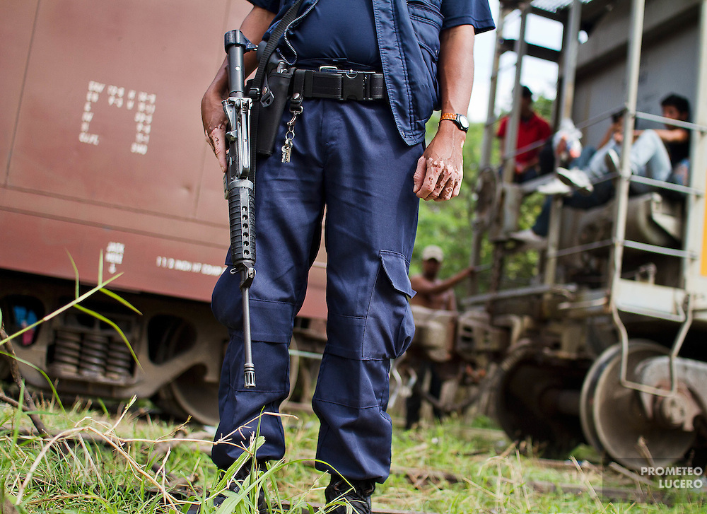 """A municipal policeman stands next to the train, nicknamed """"La Bestia"""". Local authorities have been accused of being involved with organised crime bands on kidnapping. (Photo: Prometeo Lucero)"""