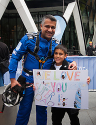 London, September 7th 2015. PICTURED: 30 St Mary's Axe Building Manager Jimmy Demetriou gets a hug from his son Joseph who made a special banner in support of his Dad's abseil down the face of the iconic Building he manages. The Outward Bound Trust City Three Peaks Challenge in conjunction with The Royal Navy and Royal Marines Charity is a breathtaking abseiling endeavour on the greatest urban mountain range: The City of London.
