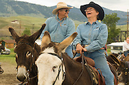 Cowgirl and Cowboy couple riding donkeys (Equus asinus) at Montana Mule Days, Drummond, Montana, <br /> MODEL RELEASED