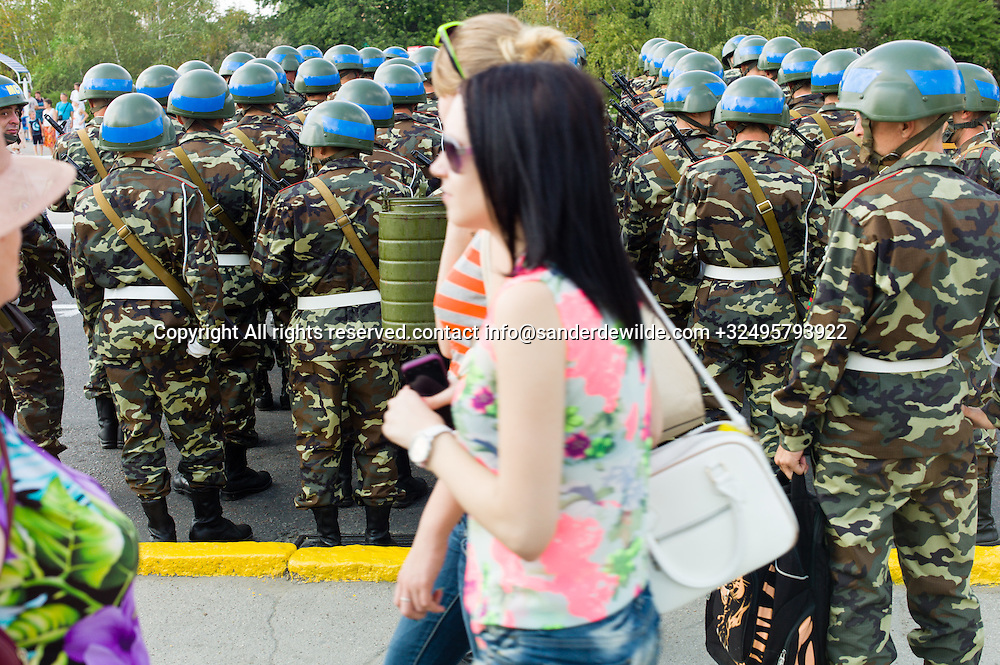 20150831 Moldova, Transnistria,Pridnestrovian Moldavian Republic (PMR) Tiraspol. Rehersal for the big parade, in the 25th  Transnistrian independance day when  they had a war separating from Moldova.Transnistrian girls pass by while the Transnistrian peace corps is in the middle of rehearsals.