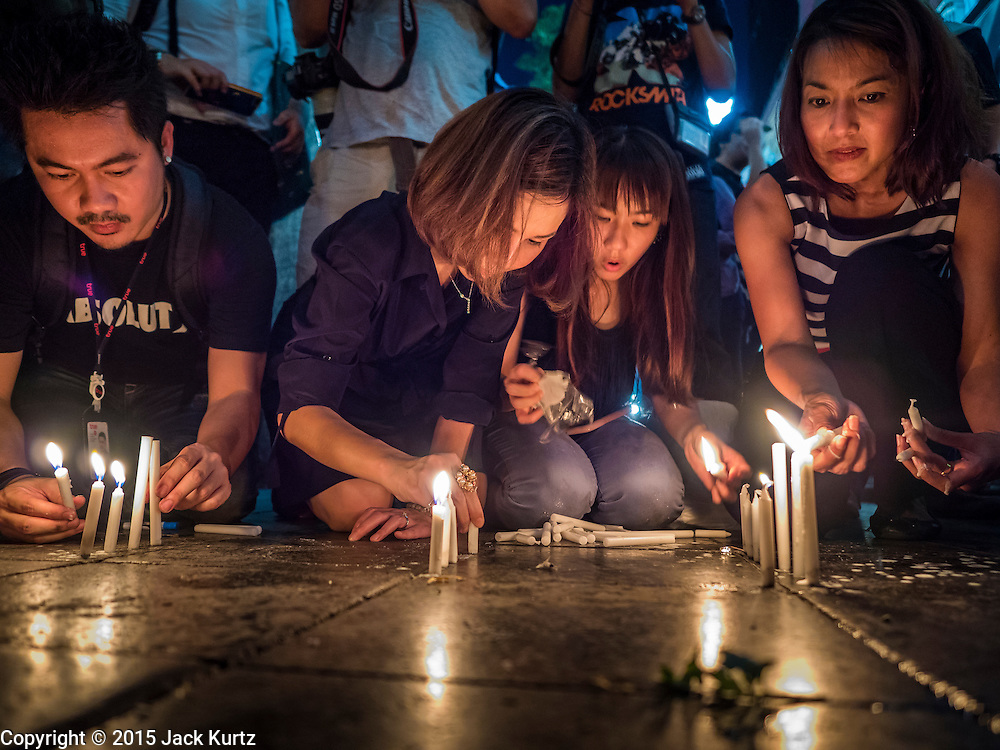 18 AUGUST 2015 - BANGKOK, THAILAND: People light candles to honor the deceased at a makeshift memorial in front of Erawan Shrine, which was damaged by a bomb Monday night. An explosion at Erawan Shrine, a popular tourist attraction and important religious shrine in the heart of the Bangkok shopping district, killed at least 20 people and injured more than 120 others, including foreign tourists, during the Monday evening rush hour. Twelve of the dead were killed at the scene. Thai police said an Improvised Explosive Device (IED) was detonated at 18.55. Police said the bomb was made of more than six pounds of explosives stuffed in a pipe and wrapped with white cloth. Its destructive radius was estimated at 100 meters.     PHOTO BY JACK KURTZ