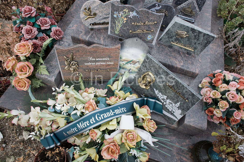 """Detail of wreaths to a mother and grandmother on a recent grave in a rural french hamlet in Indre-et-Loir. The French inscription reads """"To our mother and grandmother"""" and faded flower petals surround the ribbon with other family members having purchased memorial plaques from a nearby monumental masons."""