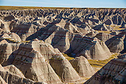 Striped rock layers in Badlands National Park, South Dakota, USA. The intricately carved cliff of the Badlands Wall constantly retreats as it erodes and washes into the White River Valley below.