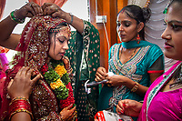 Labasa, Fiji | 2012<br /> Bhawna's relatives dress her in her wedding sari during her marriage ceremony to Arvendra. Arvendra's parents work in the cane fields, while he is a manager in an insurance company. Bhawna studied at the University of the South Pacific in Suva, Fiji's capital city. Like most of their generation of Indo-Fijians, they will work in professions far from the cane fields.