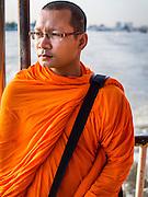 21 OCTOBER 2014 - BANGKOK, THAILAND:  A Buddhist monk on a Chao Phraya River Express Boat going down the Chao Phraya River at the end of the day.   PHOTO BY JACK KURTZ