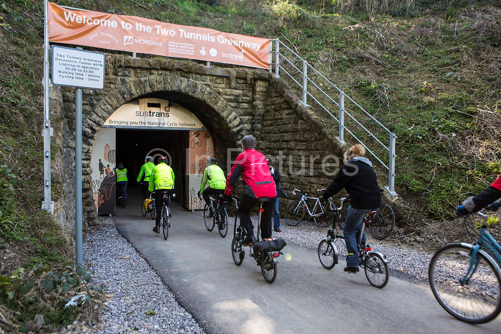 Cyclists entering the restored Devonshire Tunnel as part of the Two Tunnels Greenway near Bath, Somerset, England, United Kingdom on 6th April 2013.  The cyclists will enjoy he fantastic 13-mile circular route from the centre of Bath that takes in National Cycle Route 24 and National Route 4 and the spectacular Dundas Aqueduct on the Kennet & Avon Canal.  The opening of this route has been organised by Sustrans in partnership with Bath and North East Somerset Council.  This tunnel was previously a railway tunnel on one of the United Kingdoms most famous rail lines. The tunnel is 407 meters long and stone-lined throughout.  It has been restored to make it accessible by foot, cycle or wheelchair and is part of a 13-mile circuit.  The event was attended by hundreds of cyclists and pedestrians of all ages and abilities.