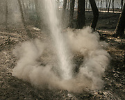 After a vast forest fire, a firefighting truck hoses a mix of pressured water and wetting agent deep into the ground. The lower part of the humus is still smoldering and ejecting smoke and CO2, so it's important to reach deep in the ground.<br /> Bordeaux, France.