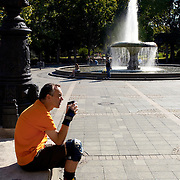 man wearing rollerblades sitting in city park holding a hot drink