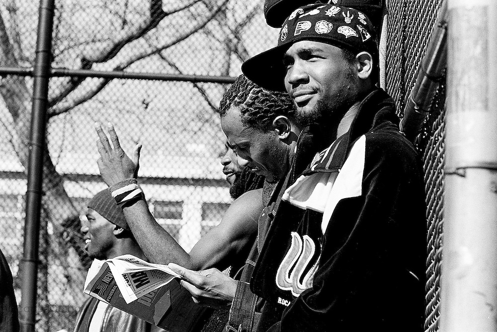 """April 9th 2005. New York, New York. United States..Located in the heart of Greenwich Village, the West 4th Street basketball Court, known as """"The Cage"""", offers no seating but attracts the best players and a lot of spectators as soon as spring is around the corner..Half the size of a regular basketball court, it creates a fast, high level of play. The more people watch, the more intense the games get. « The Cage » is a free show. Amazing actions, insults and fights sometimes, create tensions among and inside the teams. The strongest impose their rules. Charisma is present..""""The Cage"""" is a microcosm. It's a meeting point for the African American street culture of New York. Often originally from Jamaica or other islands of the Caribbean, they hang out, talk, joke, laugh, comment the game, smoke… Whether they play or not, they're here, inside """"The Cage"""". Everybody knows everybody, they all greet each other, they shake hands and hug: """"Yo, whasup man?"""""""