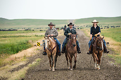 "The Nature Conservancy's Matador Ranch Operations Manager Charlie Messerly, left, Jason Hanlon and Marisa Lipsey works with  ranching families in Eastern Montana  at the Matador ranch ""grass bank"". The ""grass bank"" is an innovative way to leverage conservation gains, in which ranchers can graze their cattle at discounted rates on Conservancy land in exchange for improving conservation practices on their own ""home"" ranches. In 2002, the <br /> Conservancy began leasing parts of the ranch to neighboring ranchers who were suffering from  severe drought, offering the Matador's grass to neighboring ranches in exchange for their  participation in conservation efforts. The grassbank has helped keep ranchers from plowing up native grassland to farm it; helped remove obstacles to pronghorn antelope migration; improved habitat for the Greater Sage-Grouse and reduced the risk of Sage-Grouse colliding with fences; preserved prairie dog towns and prevented the spread of noxious weeds. (Photo By Ami Vitale)"