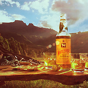 Outdoor table with whisky bottle and glasses on it including a saddle, riding hat and whip Ray Massey is an established, award winning, UK professional  photographer, shooting creative advertising and editorial images from his stunning studio in a converted church in Camden Town, London NW1. Ray Massey specialises in drinks and liquids, still life and hands, product, gymnastics, special effects (sfx) and location photography. He is particularly known for dynamic high speed action shots of pours, bubbles, splashes and explosions in beers, champagnes, sodas, cocktails and beverages of all descriptions, as well as perfumes, paint, ink, water – even ice! Ray Massey works throughout the world with advertising agencies, designers, design groups, PR companies and directly with clients. He regularly manages the entire creative process, including post-production composition, manipulation and retouching, working with his team of retouchers to produce final images ready for publication.