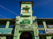 """09 NOVEMBER 2014 - SITTWE, RAKHINE, MYANMAR:  The """"New Market,"""" built in 1956, in Sittwe. The market building is closed, but vendors still set up in the open space behind the building and under the eaves of the building. Sittwe is a small town in the Myanmar state of Rakhine, on the Bay of Bengal. PHOTO BY JACK KURTZ"""