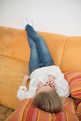 Teenage girl lying and talking on cell phone
