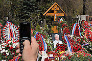 Moscow, Russia, 26/04/2007..Russians visit Boris Yeltsin's grave to pay their last respects after Novodevichy Cemetery was  reopened to the public on the day following the former Russian President's funeral. A mourner photographs the grave on his mobile telephone..