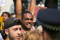 London, June 21st 2017. Protesters march through London from Sheherd's Bush Green in what the organisers call 'A Day Of Rage' in the wake of the Grenfell Tower fire disaster. The march is organised by the Movement for Justice By Any Means Necessary and coincides with the Queen's Speech at Parliament, the destination. PICTURED: The heat of the day and the exertion of the march shows in this protester's face.