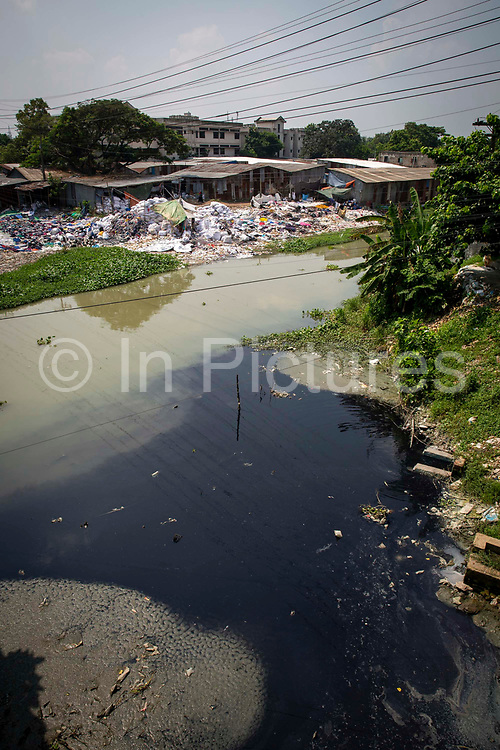 Black water probably dye enters the river from a factory,  environmental pollution on the river banks surrounding some of the textile industry buildings of Savar Upazila on 30th September 2018 in Dhaka, Bangladesh. The garment business is the main industry of Savar Upazila, a district in the northern part of Dhaka.
