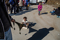MYTILINI, GREECE - FEBRUARY 09: A father pulls his son in a fruit crate to entertain him while waiting for register their names at the registration tent inside Moria refugee camp after their arrival by dinghy to a Lesvos beach on February 09, 2015 in Mytilini, Greece. After travelling for more than two hours crossing the Aegean sea, refugees are picked up by buses run by UNHCR and transferred to the Moria refugee camp where they have to register their names. As thousands of refugees arrive everyday in Lesvos, queues for registration can take up to two days. In the camp several international organisations provide assistance to the refugees as food, medical assistance, blankets and clothes among other items and services. Photo: © Omar Havana. All Rights Are Reserved