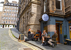 Edinburgh, Scotland, UK. 12 July, 2020, Business slowly returning to normal in Edinburgh city centre. Tourists still almost non existent and streets remain very quiet in the Old Town. Outdoor seating areas of cafes are now open in the Old Town. Iain Masterton/Alamy Live News