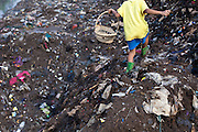 A boy picks through trash and collects scrap metal by the Citarum river in Kampung Bolero, Dayeuhkolot district, Bandung regency, Indonesia. Sludge and trash dredged from the riverbed is now piled up on the riverbank. ..The Citarum river, which runs about 270 kilometers through the province of West Java, is considered to be among the world's dirtiest. Over the last twenty years, the river has been severely polluted by toxic industrial waste, trash and raw sewage. The Citarum is one of the main sources of freshwater for West Java and supplies about 80% of water for Indonesia's capital Jakarta.