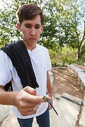 Holding and examining green darner dragonfly,  Mitchell Lake Audubon Center, San Antonio, Texas, USA.