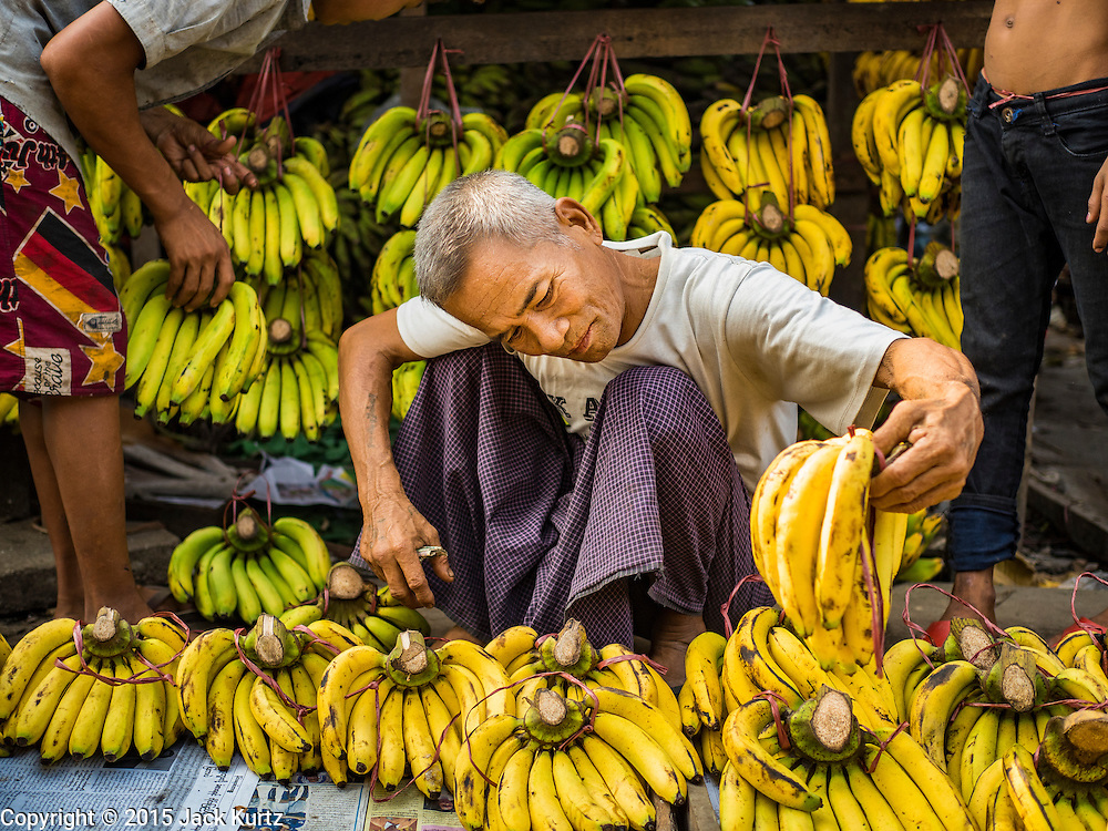 """25 OCTOBER 2015 - INSEIN, MYANMAR:  Selling bananas at Danyin Market (also known as Da Nyin) in Insein, Myanmar, about 90 minutes from Yangon. Vendors in the market sell just about everything people in the area need, but mostly it's a """"wet market"""" with fruits, vegetables and meats. Most people in Myanmar still do not have refrigerators in their homes, so people go to market almost every day.    PHOTO BY JACK KURTZ"""