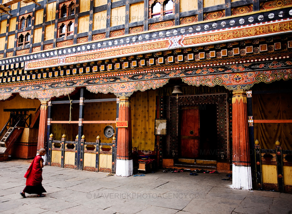 A  young monk walks though Rinpung Dzong, Paro.  Commonly described as the last Himalayan Shangrila, Bhutan is a country of unique serenity, harmony, and beauty. Nestled between India, China, and Tibet, this independent country whose name translates as 'the Land of the Thunder Dragon' has for the past 300 years  proactively followed a policy of isolation and cultural protection. Travel in and out of the country is strictly regulated, and the impact of outside influences on the local culture is carefully monitored. Spirituality is an important aspect of Bhutanese culture, with Buddhism being interlinked with everyday life. Gross National Happiness (GNH), as opposed to GNP/GDP, forms the cornerstone of its development strategy which focuses on a holistic development strategy that complements its cultural and Buddhist spiritual values.