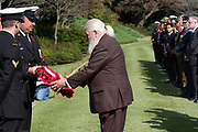 A dignitary from the Royal British Legion collects a wreath of poppies to lay at the Cross of Sacrifice during the Remembrance Sunday ceremony at the Hodogaya, Commonwealth War Graves Cemetery in Hodogaya, Yokohama, Kanagawa, Japan. Sunday November 11th 2018. The Hodagaya Cemetery holds the remains of more than 1500 servicemen and women, from the Commonwealth but also from Holland and the United States, who died as prisoners of war or during the Allied occupation of Japan. Each year officials from the British and Commonwealth embassies, the British Legion and the British Chamber of Commerce honour the dead at a ceremony in this beautiful cemetery. The year 2018 marks the centenary of the end of the First World War in 1918.
