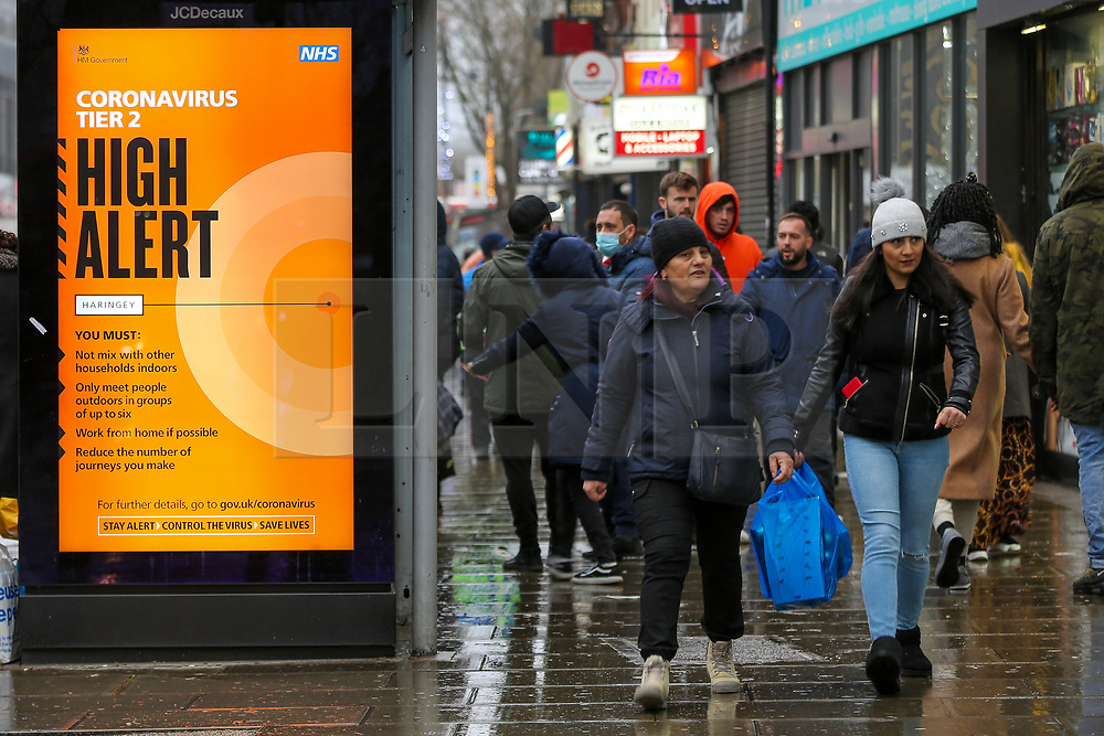 © Licensed to London News Pictures. 13/12/2020. London, UK. Shoppers without wearing face coverings walk past the 'Coronavirus Tier 2 High Alert' COIVD-19 public information campaign digital poster in north London amid fears of London going into Tier 3 lockdown restrictions, as the coronavirus infection rate in London is the highest, in England. Photo credit: Dinendra Haria/LNP