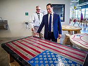 15 APRIL 2019 - DES MOINES, IOWA: JULIÁN CASTRO (right) listens to CHRIS MIES, a carpentry teacher, describe how a table with an American flag on it was made during Castro's visit to the Central Campus Skilled Trades Alliance at the Des Moines Public School's Central Campus Monday. Castro is on his third visit to Iowa since declaring his candidacy for the Democratic ticket of the US Presidency. Casto talked to students and administrators about skilled trades education and toured the campus. Iowa traditionally hosts the the first selection event of the presidential election cycle. The Iowa Caucuses will be on Feb. 3, 2020.                PHOTO BY JACK KURTZ