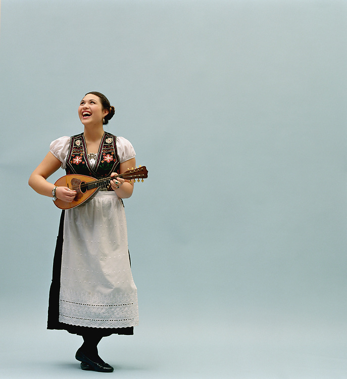 Young woman wearing traditional Scandinavian outfit holding zither, laughing in a studio portrait