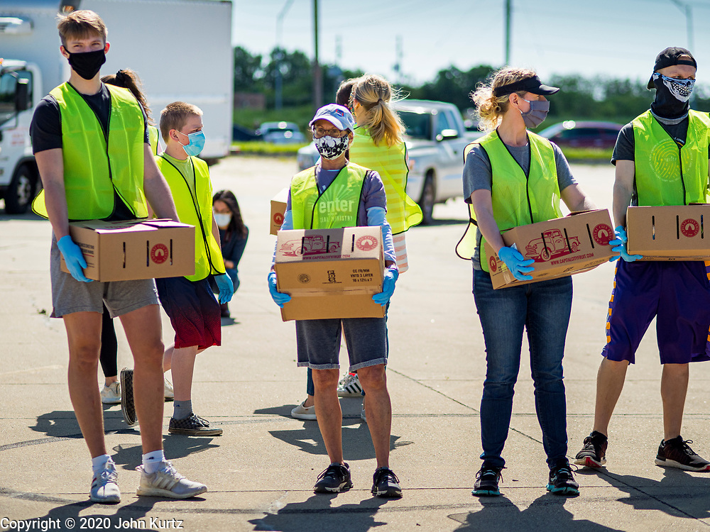 29 MAY 2020 - DES MOINES, IOWA: Volunteers wait to carry boxes of produce to motorists at a produce distribution in a mall parking lot in Des Moines. The Des Moines Area Religious Council (DMARC) and Capitol City Fruit from Norwalk, IA, gave away 1,800 boxes of fresh produce with a mix of vegetables and fruit. The boxes contain enough produce to feed a family of four for a week. The produce was provided by the USDA Farmers to a Families food program. Because of the COVID-19 pandemic, the unemployment rate in Iowa hit 10.2% in May, the highest unemployment rate ever recorded in Iowa and food insecurity in Iowa is impacting communities throughout the state.          PHOTO BY JACK KURTZ