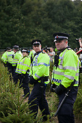 Police  lines in a field of baby Christmas trees. Anti-fracking activists join hands to surround the Cuadrilla fracking site and the police move in to try to control events. Thousands turned out for a march of solidarity against fracking in Balcombe. The village Balcombe in Sussex is the  centre of fracking by the company Cuadrilla. The march saw anti-fracking movements from the Lancashire and the North, Wales and other communities around the UK under threat of gas and oil exploration by fracking.